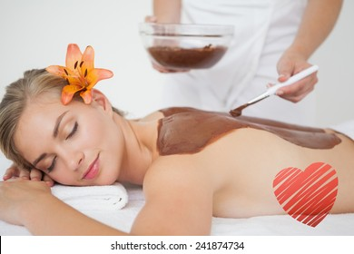 Beautiful blonde enjoying a chocolate beauty treatment against red heart