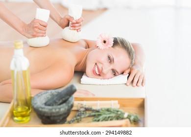 Beautiful blonde enjoying a herbal compress massage at the health spa