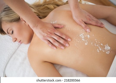 Beautiful blonde enjoying a salt scrub treatment at the health spa