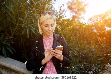 Beautiful blonde female dressed in fashionable clothes watching video on her mobile phone while relaxing outdoors in sunny day, young charming woman using cell telephone while standing in green park