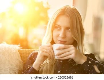 Beautiful blonde female drink coffee under sunlight