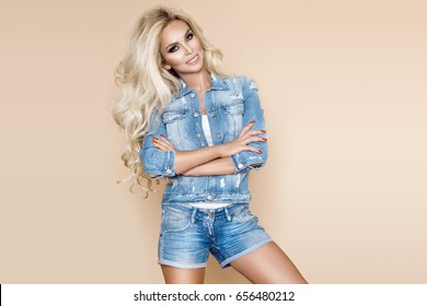 Beautiful blonde female model wearing a denim jacket and shorts on a beige background