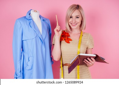 beautiful blonde female seamstress writes curve template. tailor creates a collection outfits sews clothes sewing machine in workshop. young woman designer clothes notes ideas pink background studio