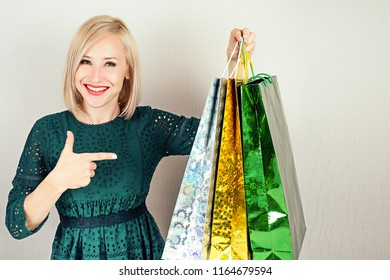 beautiful blonde female shopaholic in a green dress points finger to the shopping bags . concept of shopaholism and sales