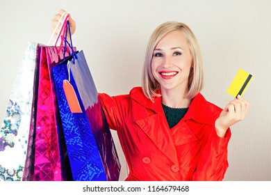 beautiful blonde female shopaholic in a red coat with shopping bags and plastic credit card . concept of shopaholism and sales