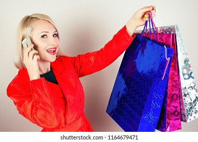 beautiful blonde female shopaholic in a red coat with shopping bags calls talks by phone . concept of shopaholism and sales