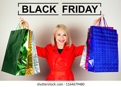 beautiful blonde female shopaholic in a red coat with shopping bags . concept of shopaholism and black friday sales
