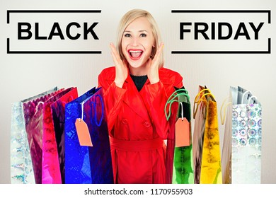 beautiful blonde female shopaholic in a red coat with shopping bags . concept of shopaholism and sales black friday