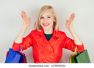beautiful blonde female shopaholic in a red coat with shopping bags . concept of shopaholism and sales