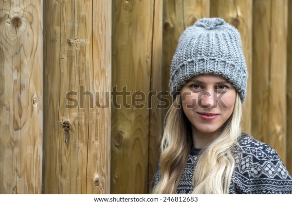 Beautiful blonde female stay uoutdoor on the wood background