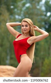 Beautiful blonde fitness girl with perfect body posing outdoor in the red swimsuit. Baywatch. Ukraine.