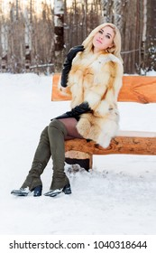 Beautiful blonde in fur coat, boots poses on wooden bench outdoor at winter day in park