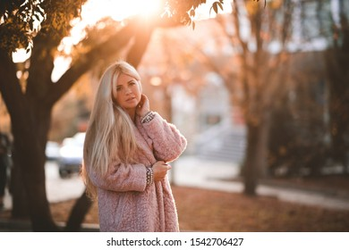 Beautiful blonde girl 20-24 year old wearing winter coat posing in city park in sun light at city background closeup. Autumn season. Looking at camera. 20s.