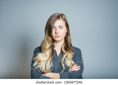 Beautiful blonde girl is angry and serious, isolated on gray background