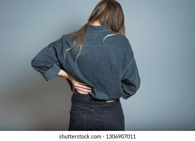 Beautiful blonde girl with back pain isolated on gray background