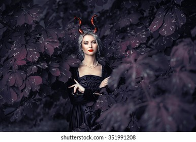 Beautiful blonde girl in a black dress with a pink medieval horns, devilish image, chestnut tree