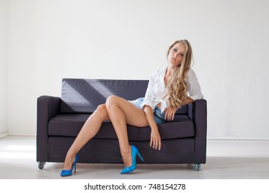 beautiful blonde girl with blue eyes sitting on the couch in a white room 1
