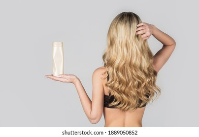 Beautiful blonde girl with a bottle of shampoos in hands. Girl with shiny and long hair. Woman long hair. Woman hold bottle shampoo and conditioner. Woman holding shampoo bottle.