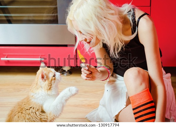 Beautiful blonde girl with candy in hand and cat sitting on a kitchen floor