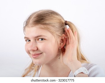 Beautiful blonde girl can't hear you - she cupping hand behind her ear and smiling