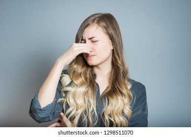 Beautiful blonde girl closes her nose because of bad smell, isolated on gray background