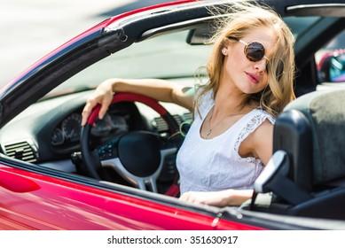 Beautiful blonde girl in a convertible car