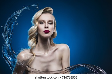 beautiful blonde girl covered with water splash on a blue background. elegant hairstyle. clear healthy skin. an evening make-up with red lips. copy space