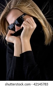 beautiful blonde girl covers her mouth with a black turtleneck on black background