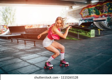 Beautiful blonde girl is doing some tricks during rollerblading. She is standing in a squat position and looking down. Her hands are aside of body. She is exercising in training room.