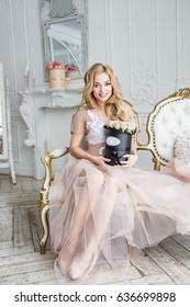 Beautiful blonde girl in dress posing in the room interior, hotel, castle, flowers
