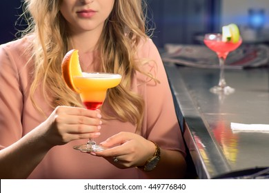 beautiful blonde girl drinking looking at martini fruity cocktail in bar fancy luxury dress gold watch