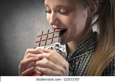 Beautiful blonde girl eating chocolate