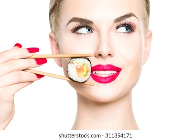 Beautiful blonde girl eating sushi close-up isolated on white. Smiled woman with perfect make up holding Sushi roll with chopsticks. Healthy Japanese food. Diet concept