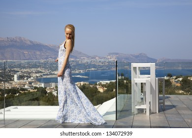 The beautiful blonde girl in a fashion blue dress on the sea