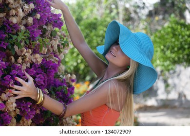 The beautiful blonde girl in the flower garden