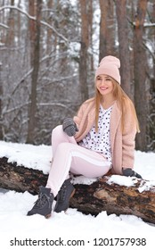 Beautiful blonde girl in the forest. A girl is sitting on a tree. She is wearing a pink hat, sweater, sweater and pants, and gray mittens. The girl smiles with teeth and looks away. Vertical photograp