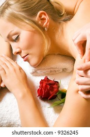 Beautiful blonde girl getting a massage and feeling visibly good about it