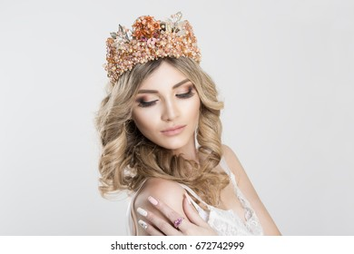 Beautiful blonde girl in a golden crown on white grey background, eyes closed looking down hand on shoulder pink ring on it
