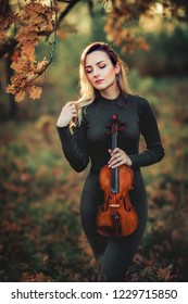 Beautiful blonde girl in green dress holding a violin in autumn park and looking down. Art work. Warm photo. Yellow background. Sad lady dreaming