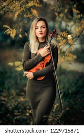 Beautiful blonde girl in green dress holding a violin in autumn park and looking  at camera. Art work. Warm photo. Yellow background. Sad lady dreaming