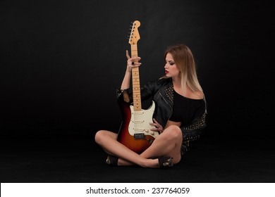 Beautiful blonde girl and guitar in rock style on a black background
