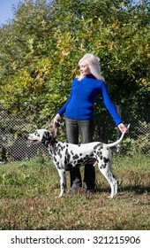 Beautiful blonde girl handler in blue sweater and black jeans on a dog exhibition in nature shows the dog breed Dalmatian in front