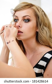 Beautiful blonde girl having makeup applied to her face, eyes and lips