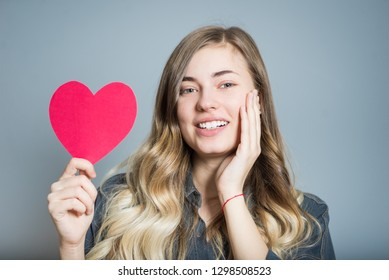 Beautiful blonde girl with a heart, Valentine's Day, isolated on gray background