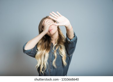 Beautiful blonde girl hides her face with hands, isolated on gray background
