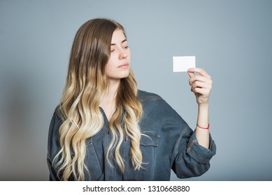 Beautiful blonde girl holding a business card, isolated on a gray background