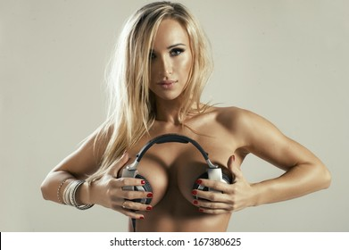 Beautiful blonde girl holding headphones on her boobs
