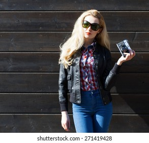 Beautiful blonde girl in huge sunglasses and a black jacket posing next to wooden wall on a sunny day with a vintage camera
