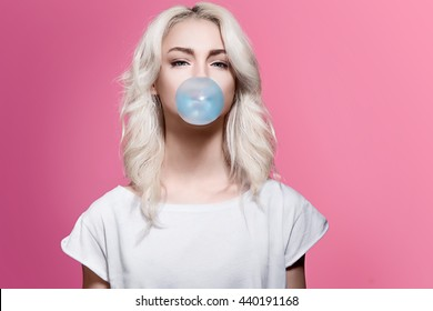 Beautiful blonde girl inflates a bubble of gum blue on a pink background