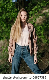 Beautiful blonde girl in jeans at sunset in nature
